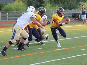 Unionville QB Alex Gorgone looks to evade Spring-Ford defenders — the junior QB had an uneven debut as a signal caller. Jim Gill photo.