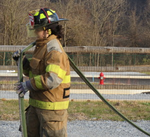 Seventeen-year-old Jordan Gusler straightens out a hose so that it can be rolled up.